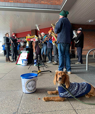 Band members busking outside Tesco with dog supporting