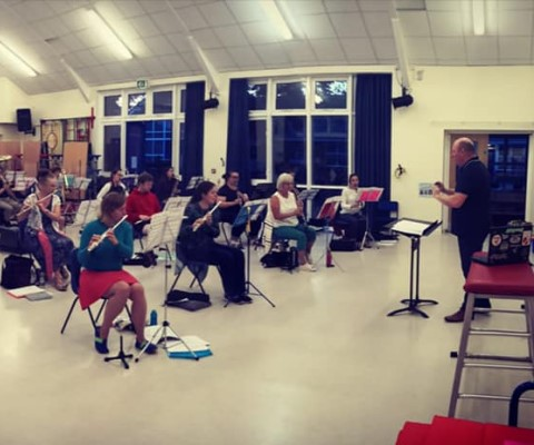 Band members and conductor socially distanced rehearsal