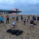 Band members picking litter on beach clean