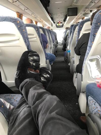 Bandmaster wearing gorilla slippers on coach