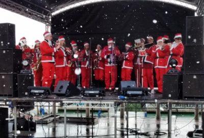 Santas playing Christmas carols on stage