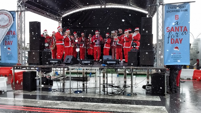 Dressed as santa claus playing Christmas carols on stage at CastlePoint